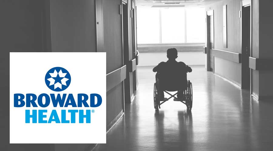 Rear view of man sitting in a wheelchair in a hallway with Broward Health's logo